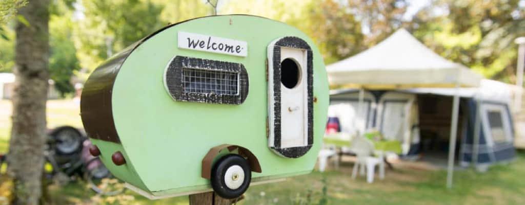 Ein kleines grünes Vogelhaus in Form eines Wohnwagen..